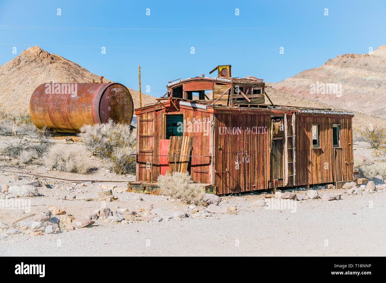 An abandoned, wheel-less Union Pacific caboose decaying in the Mojave Desert ghost town of Rhyolite. A caboose is a manned North American railroad car - Stock Image