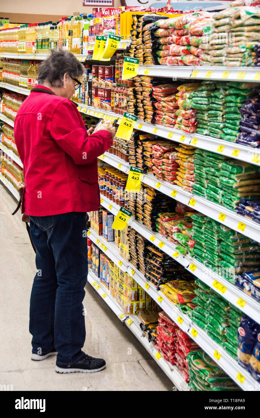 A 82 year old woman shopping for groceries at a store in Ensenada, Mexico. - Stock Image