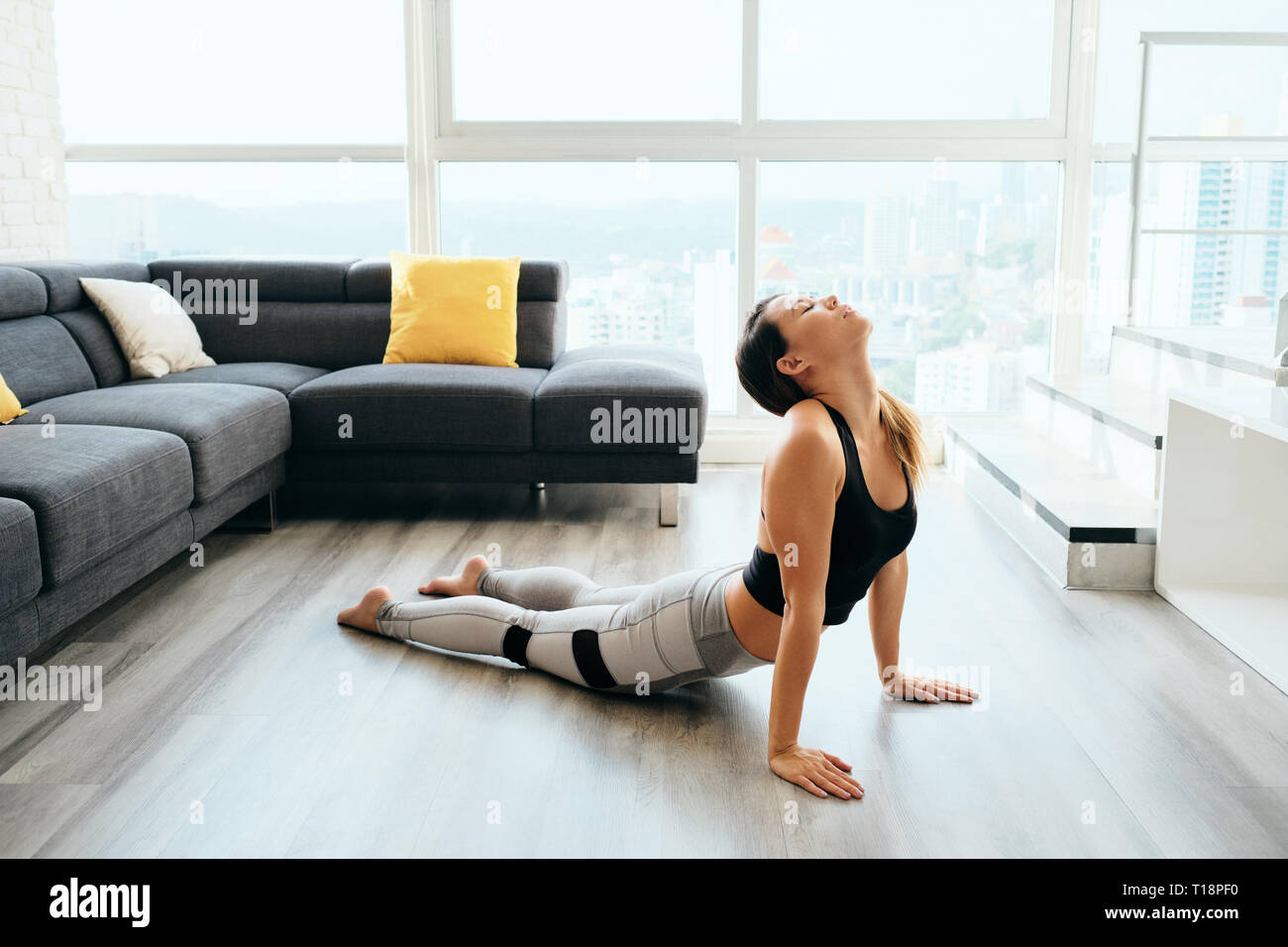 Woman Practicing Yoga At Home Doing Sun Salutation Routine - Stock Image
