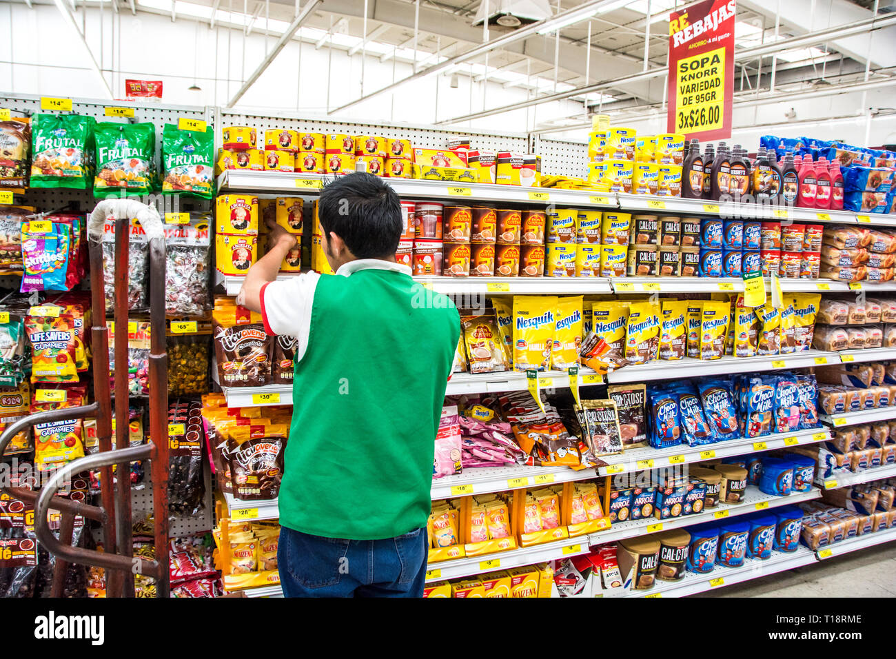 A young boy stocking shelves at a supermarket in Ensenada, Mexico. - Stock Image