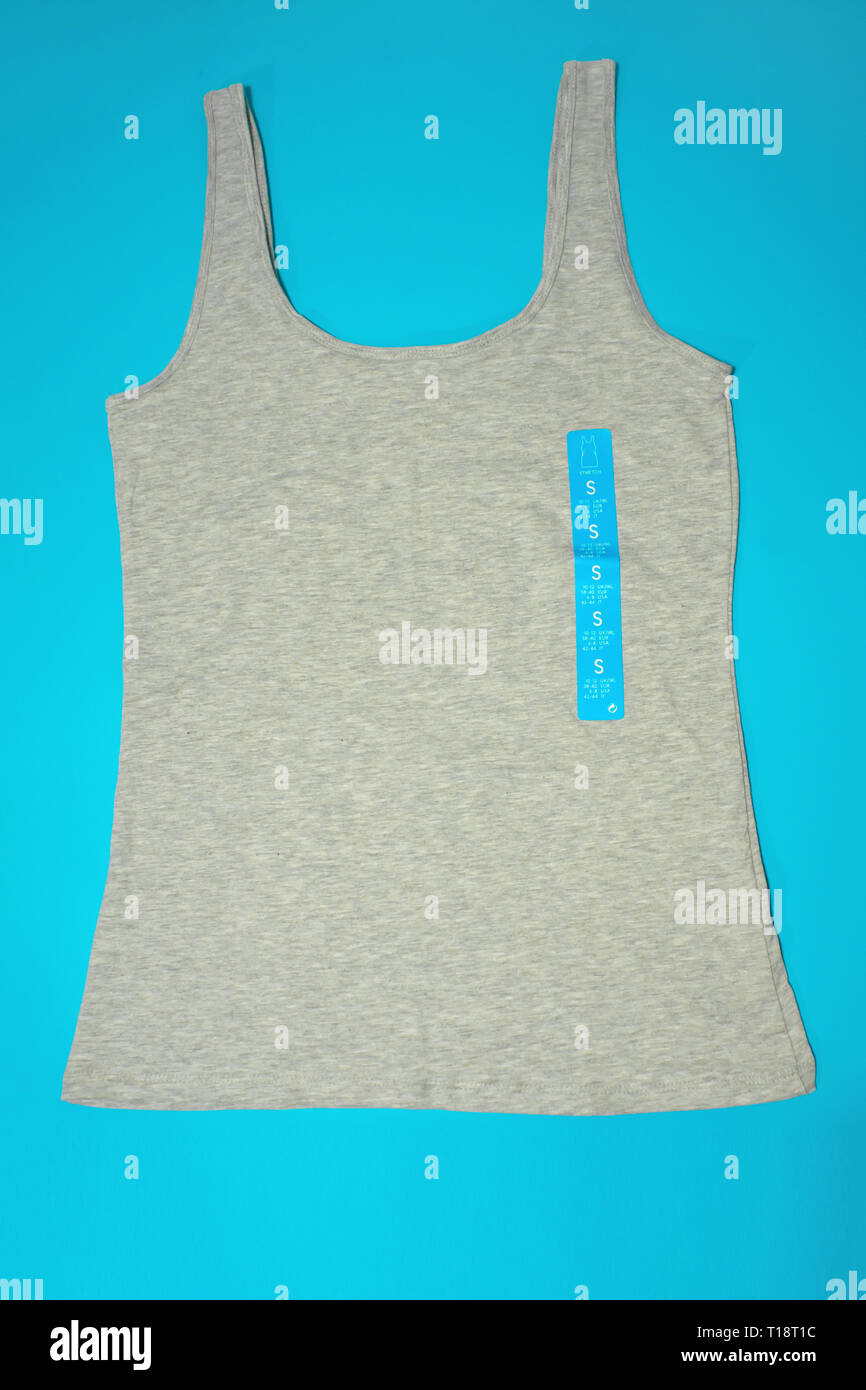 A flatlay top view of a casual gray female sleeveless top tank of a small size on blue background - Stock Image