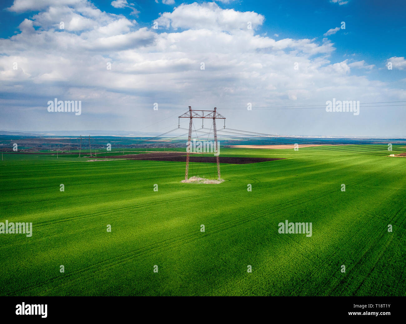 High voltage electricity pylons for power transmission in field from drone pov - Image - Stock Image