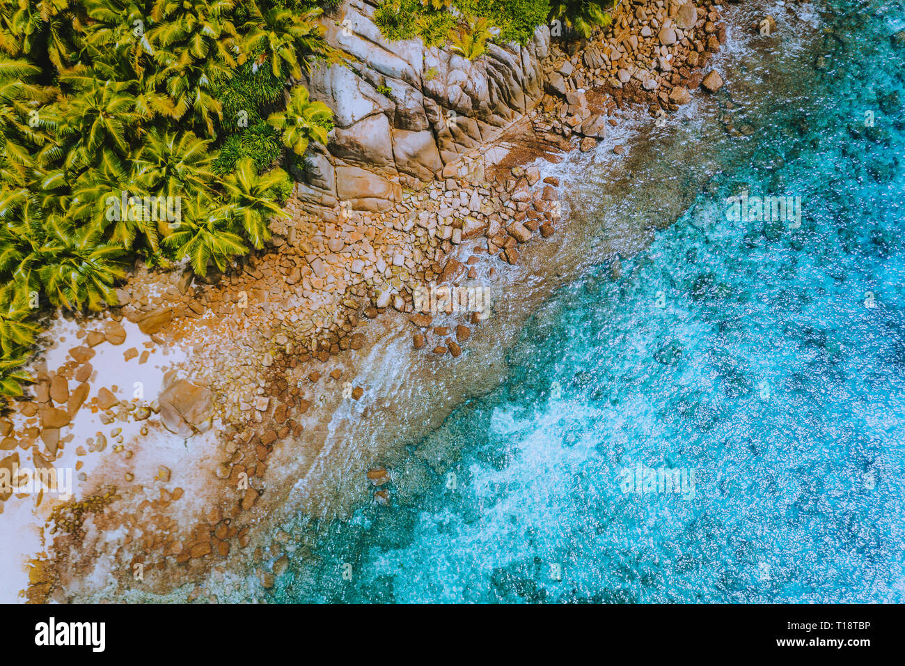 Aerial drone helicopter view of crystal clear turquoise water and amazing granite rocks. La Digue Island Seychelles - Stock Image