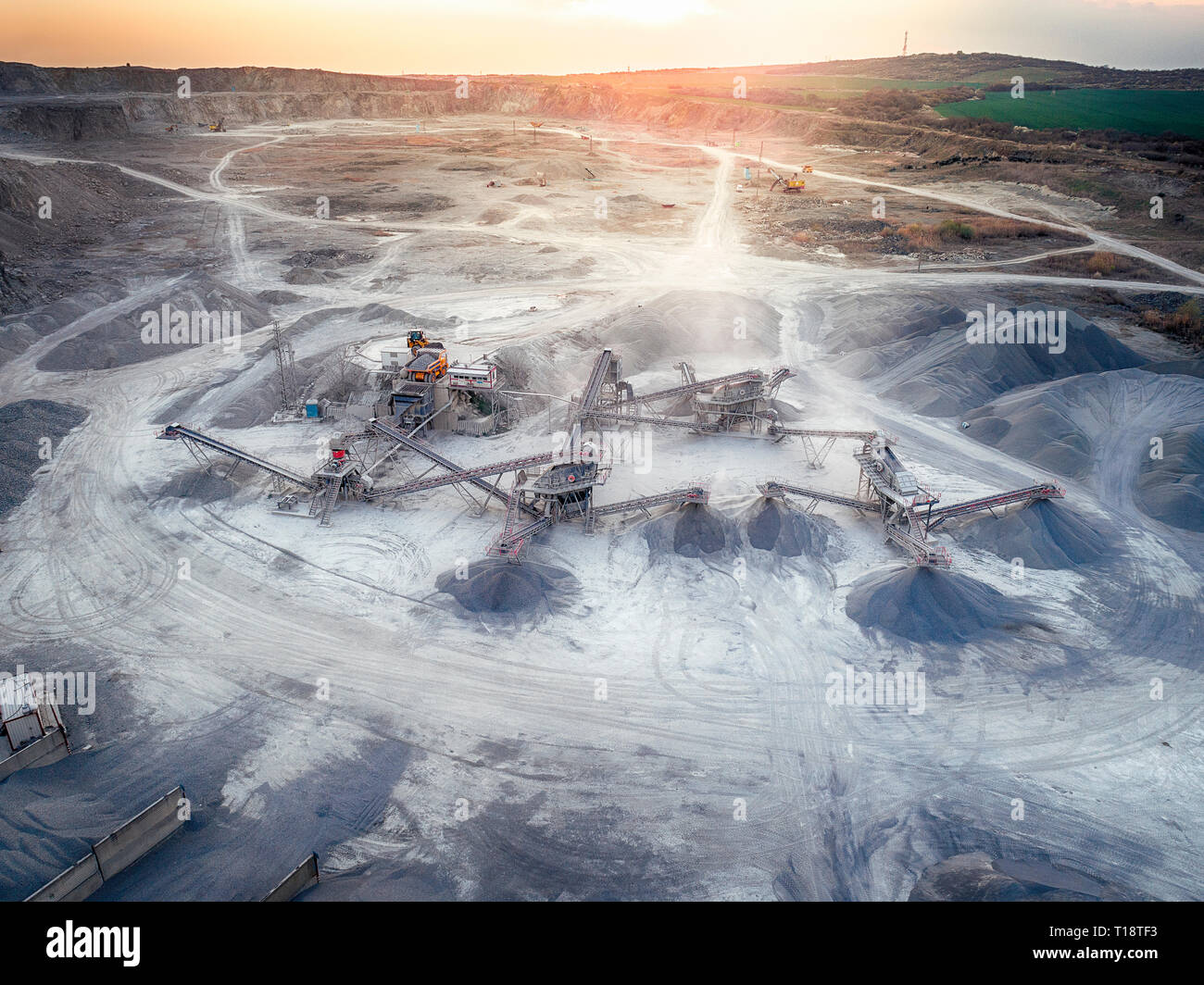 Panoramic view at sunset of gravel quarry, mining of yellow construction gravel, pumping gravel with help of powerful pumps, post-apocalyptic landscap - Stock Image