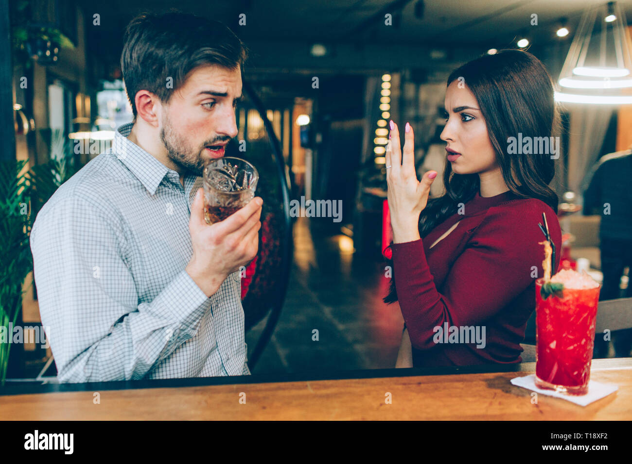 Angry young woman shows her hand with the ring on it to the man. He looks amazed. His face is full of different emotions Stock Photo