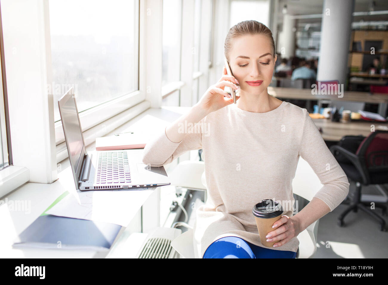 Beautiful girl is smiling. She is sitting near bright window in a beautiful sunny day and talking on the phone. She is holdin a cup of coffee and enjo Stock Photo