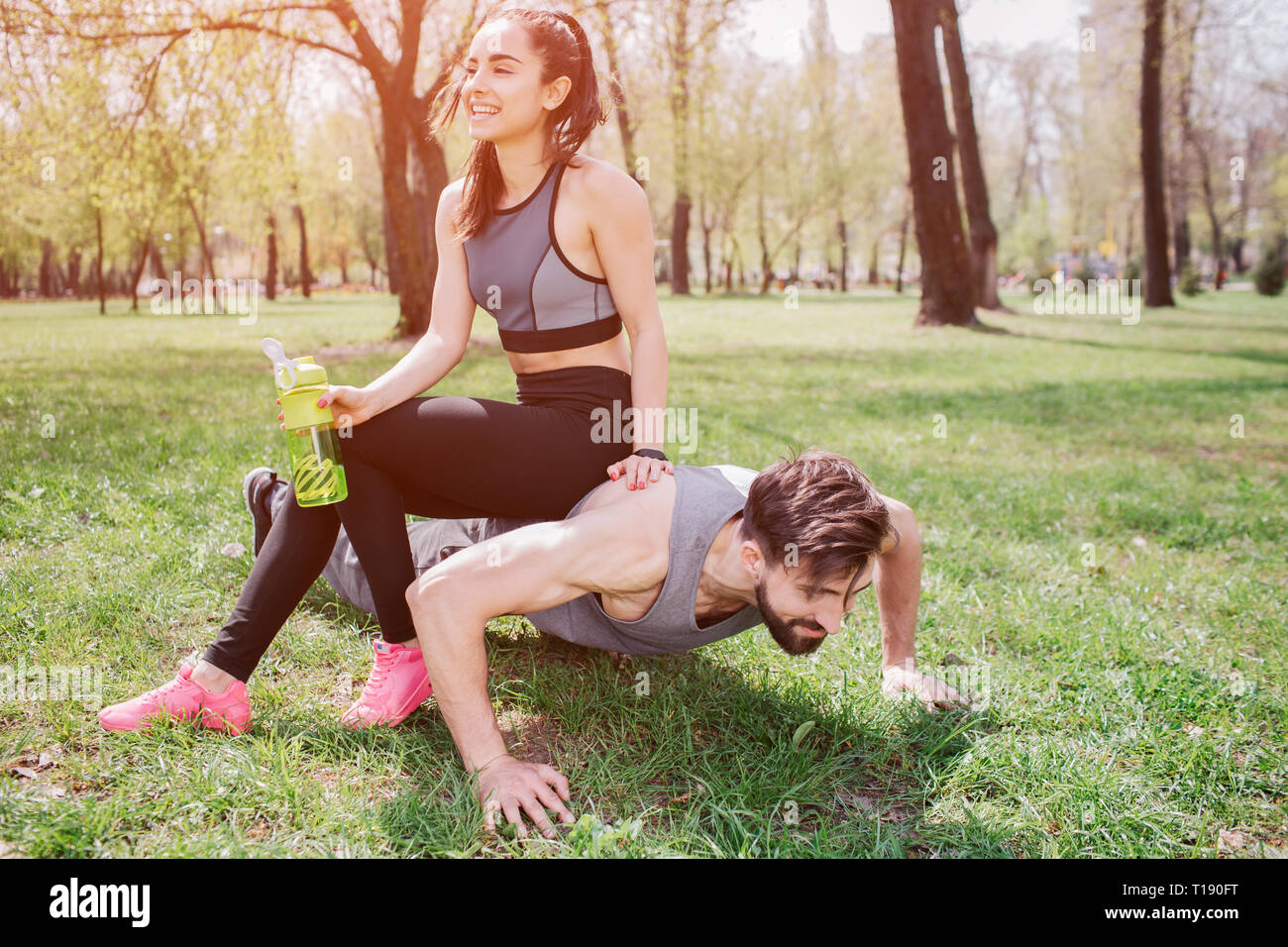 Funny picture of young man and woman. He is doing push ups and looking straight while she is sitting at him and laughing. Also girl is holding a bottl - Stock Image