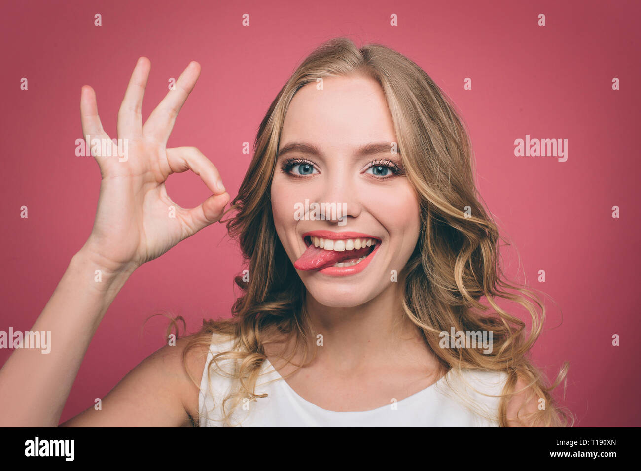 Funny young woman is looking straight forward and showing a piece of her tounge while she is smiling. Also girl is showing the ok symbol with her fing - Stock Image