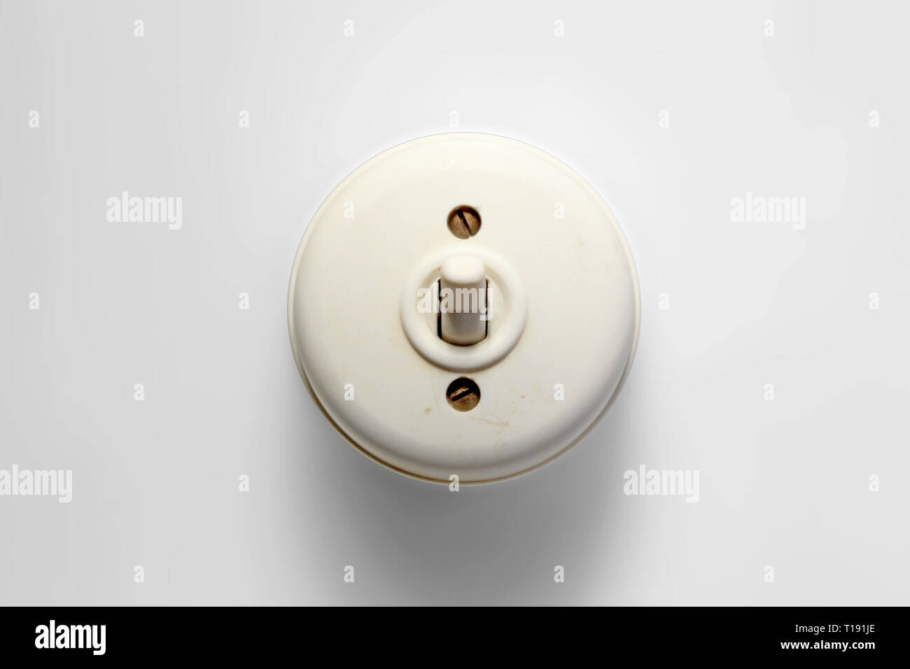Antique switch on off, white bakelite 50s/60s, isolated on white background, closeup - Stock Image