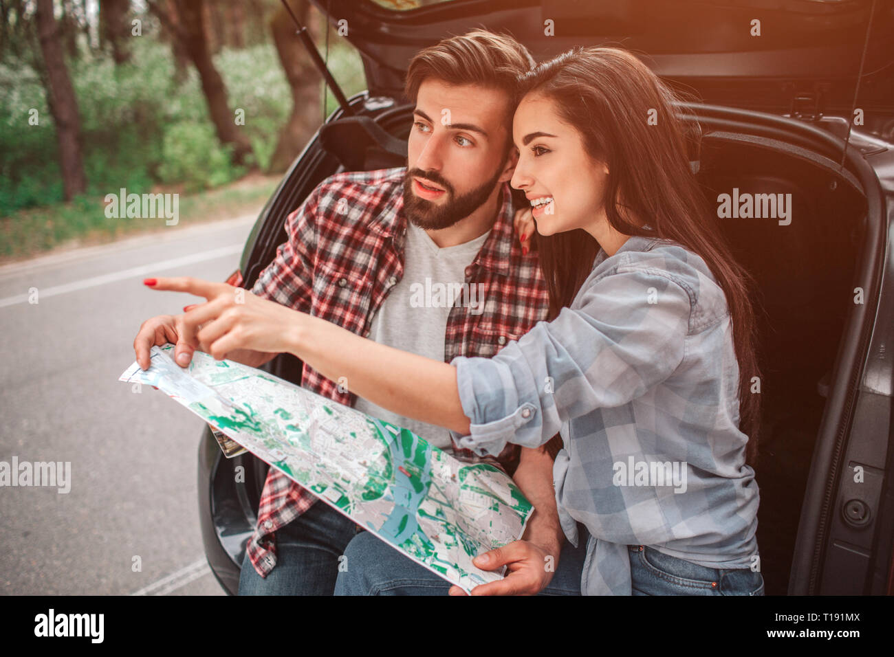 Attractive girl is sitting with her boyfriend in car's trunk and pointing straight forward. She is smiling. Guy is holding a map and looking straight  - Stock Image