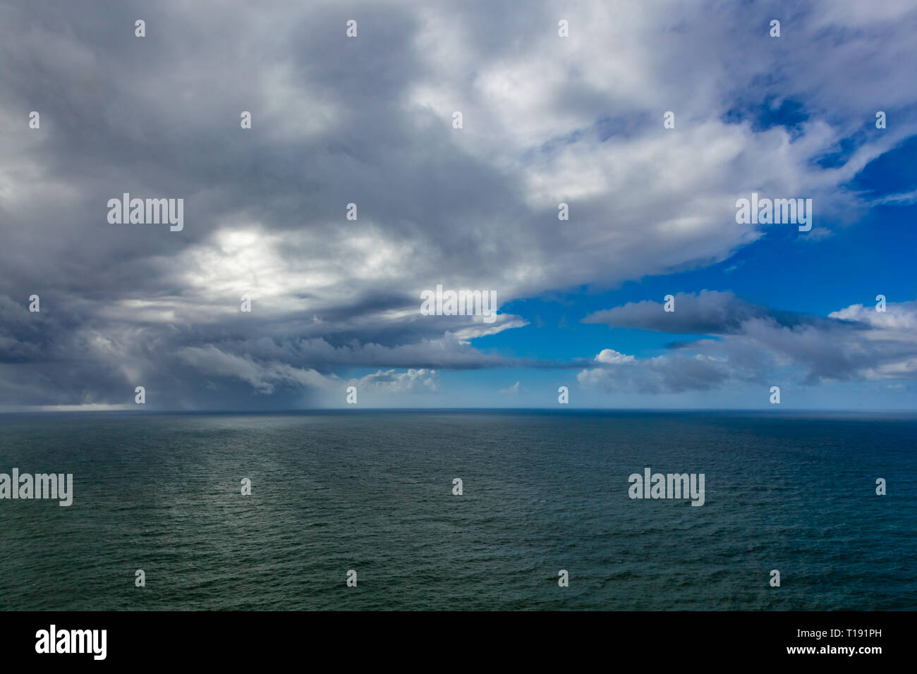 Calm flat ocean view with clouds and blue sky - Stock Image