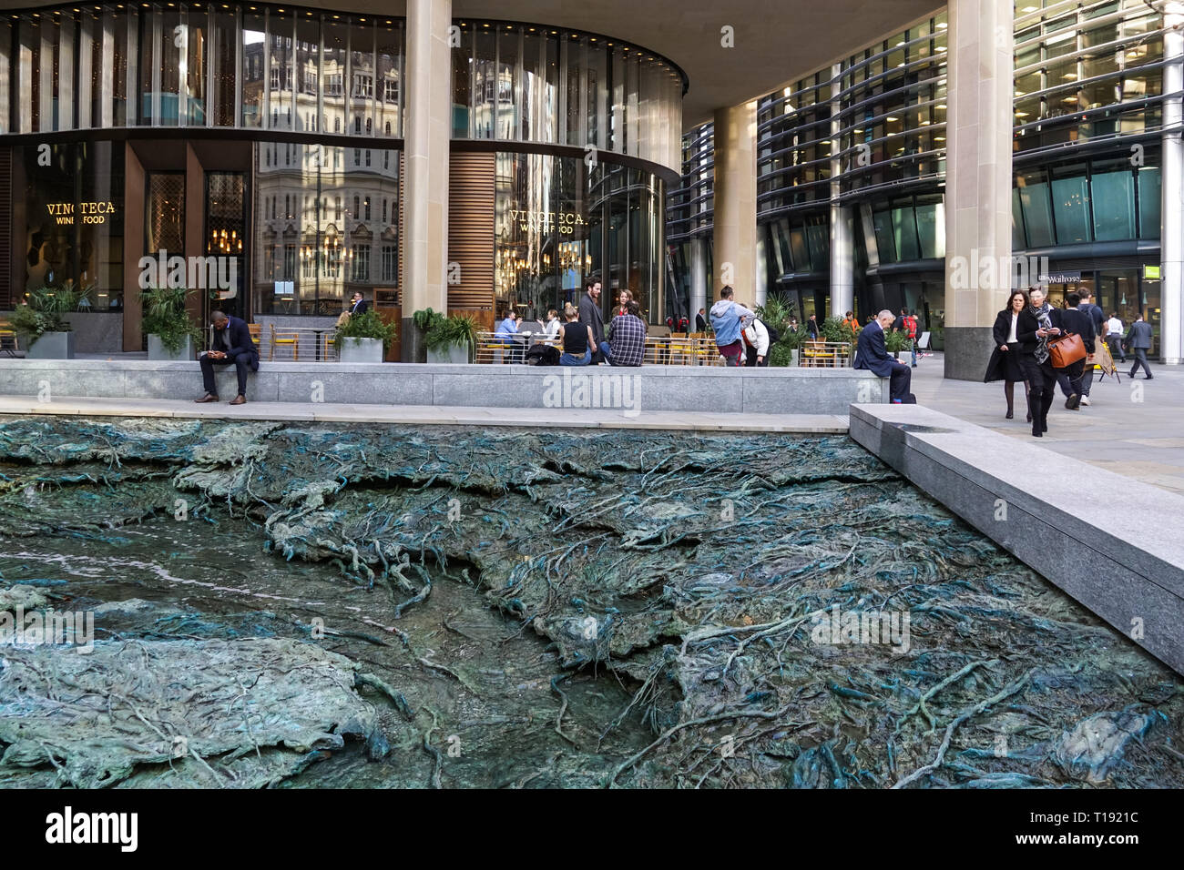 People sitting around sculpture Forgotten Streams by Cristina Iglesias at Bloomberg European Headquarters in London, England United Kingdom UK - Stock Image