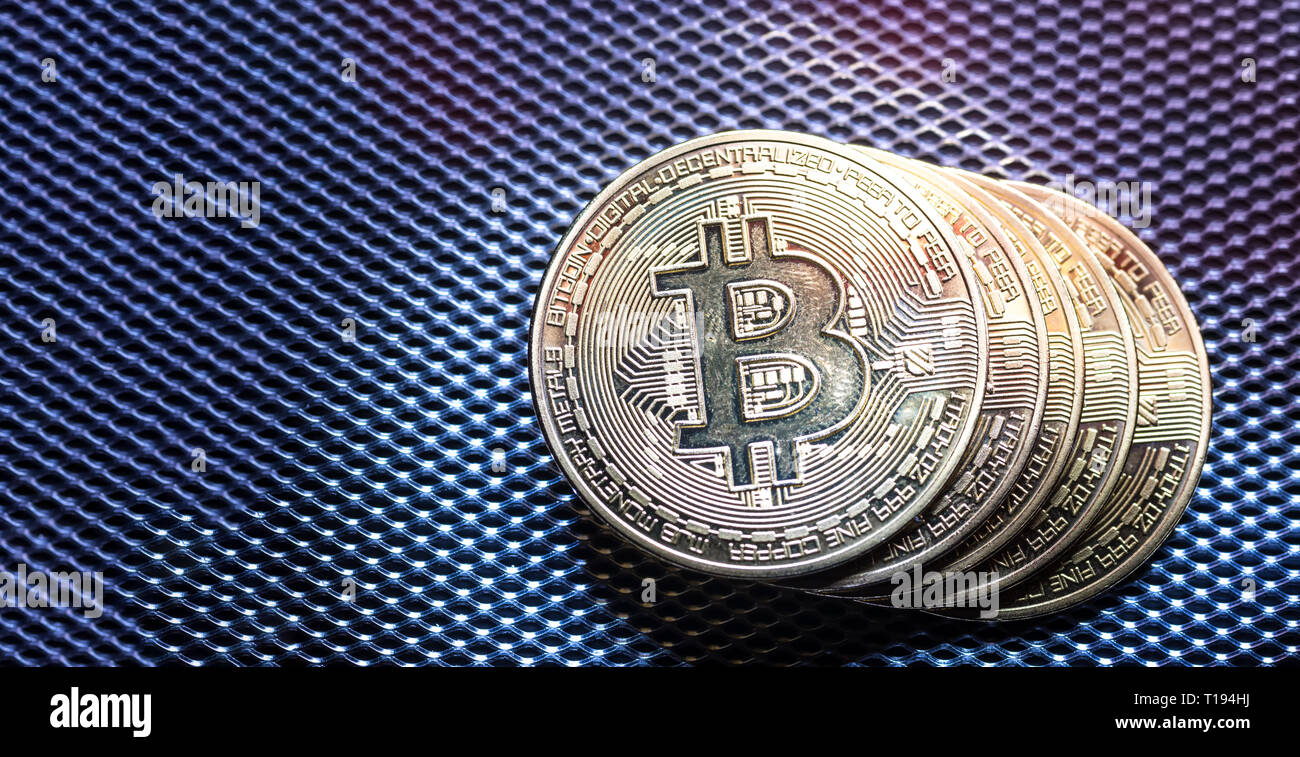 Top view of golden bit coins painted with light.Bitcoin digital currency and coin money stack on silver metallic dark background and surface Stock Photo