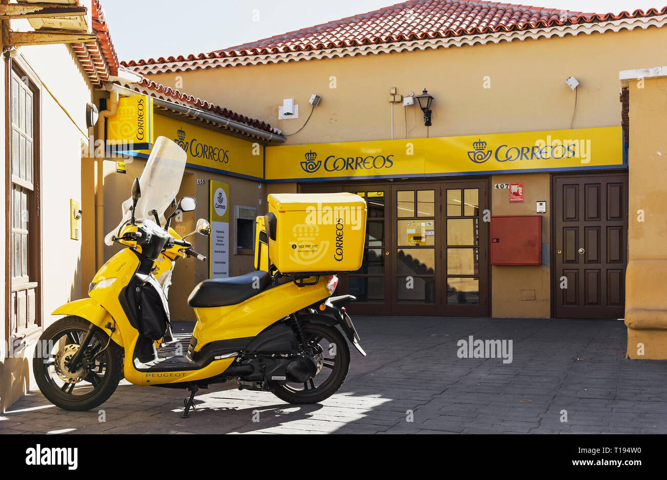 Post office and delivery scooter in yellow logo of the