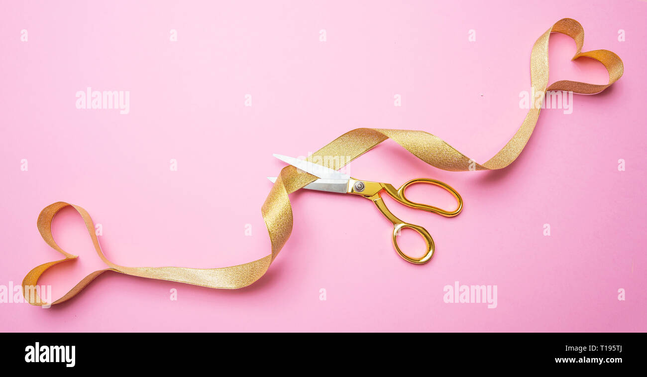 Breakup, seraration, divorce concept. Gold scissors cutting golden ribbon ending in two hearts, pink background, top view. - Stock Image