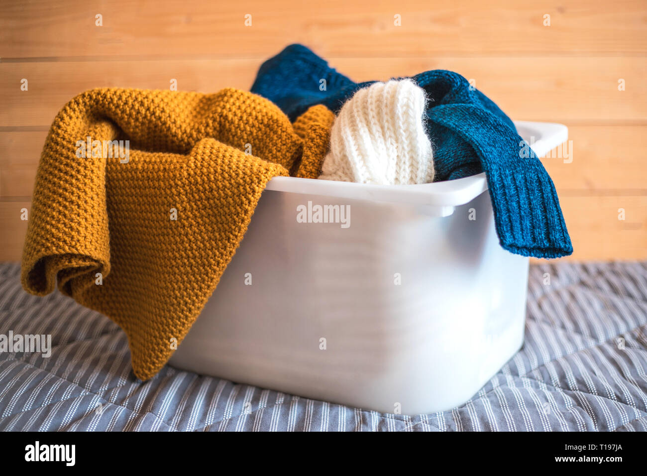 Container with laundry on sofa against wooden background. - Stock Image