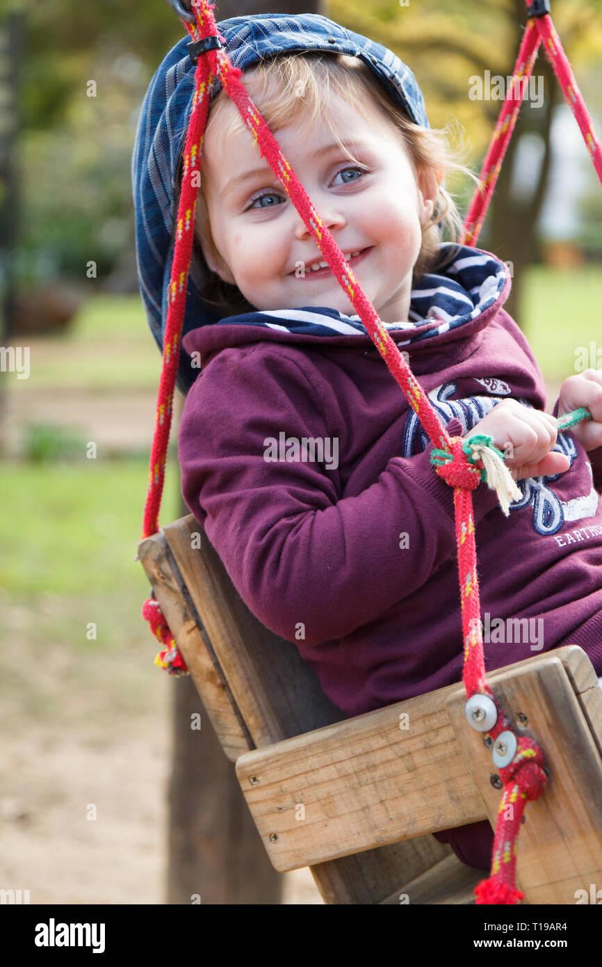 Girl child swinging on homemade swing - Stock Image