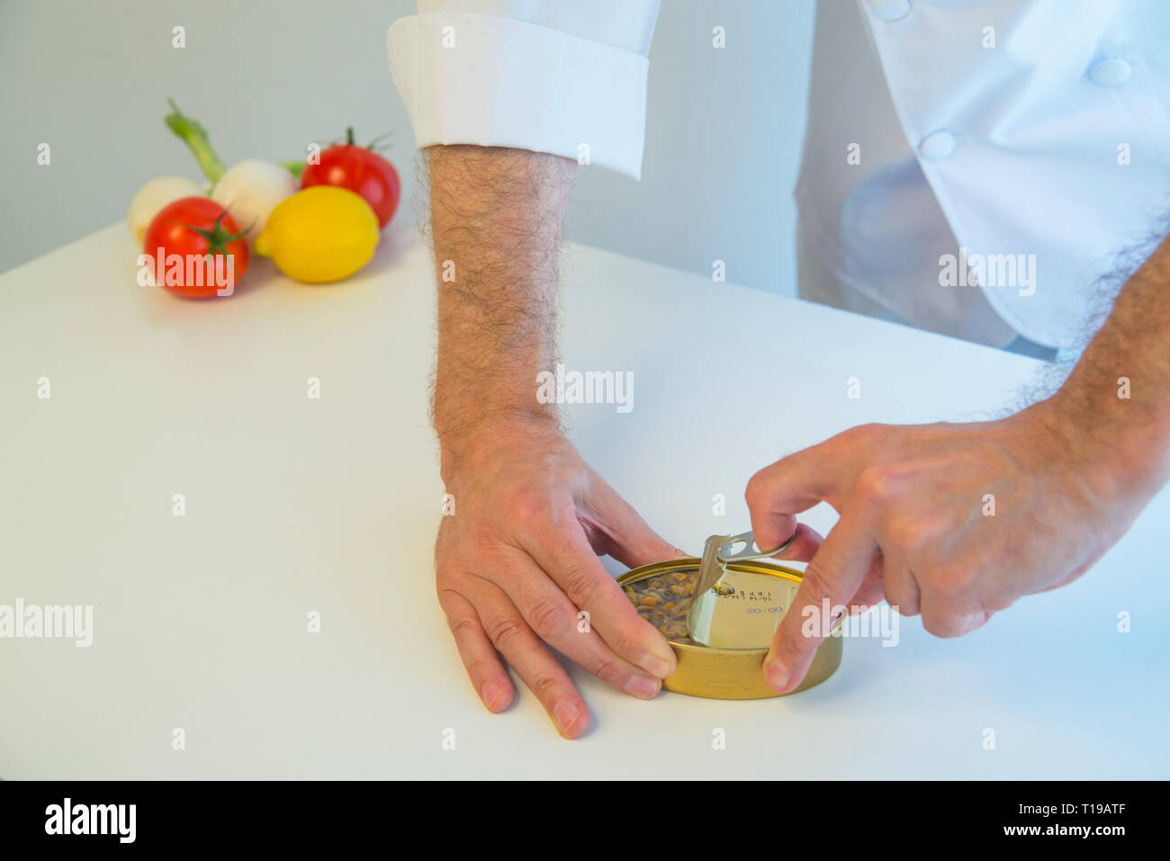 Chef opening a can of cockles - Stock Image
