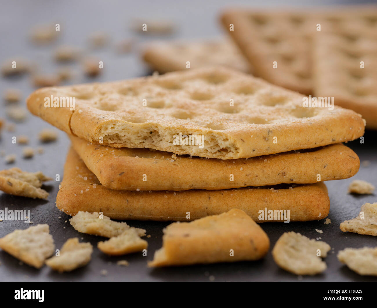 stack of square crackers with pieces and crumbs on slate gray background. Dry salt cracker cookies with fiber and dry spices - Stock Image