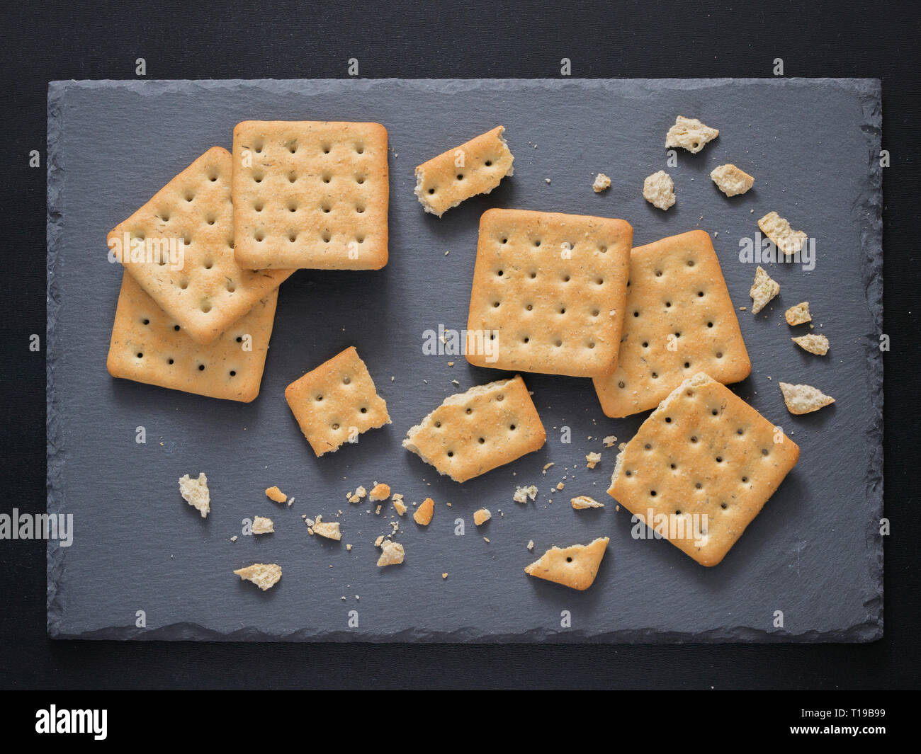 Square crackers with pieces and crumbs on slate gray background. Dry salt cracker cookies with fiber and dry spices. Top view or flat lay. Stock Photo