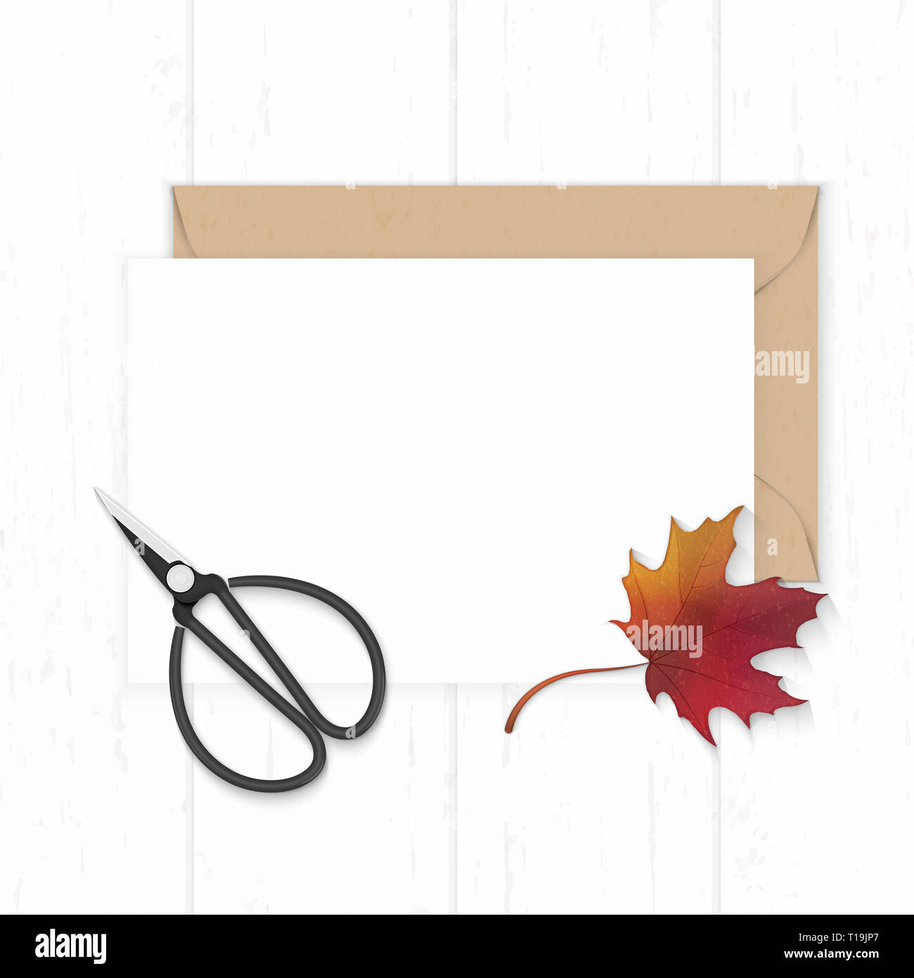Flat lay top view elegant white composition paper kraft envelope autumn red maple leaf and vintage metal scissors on wooden background. Stock Photo
