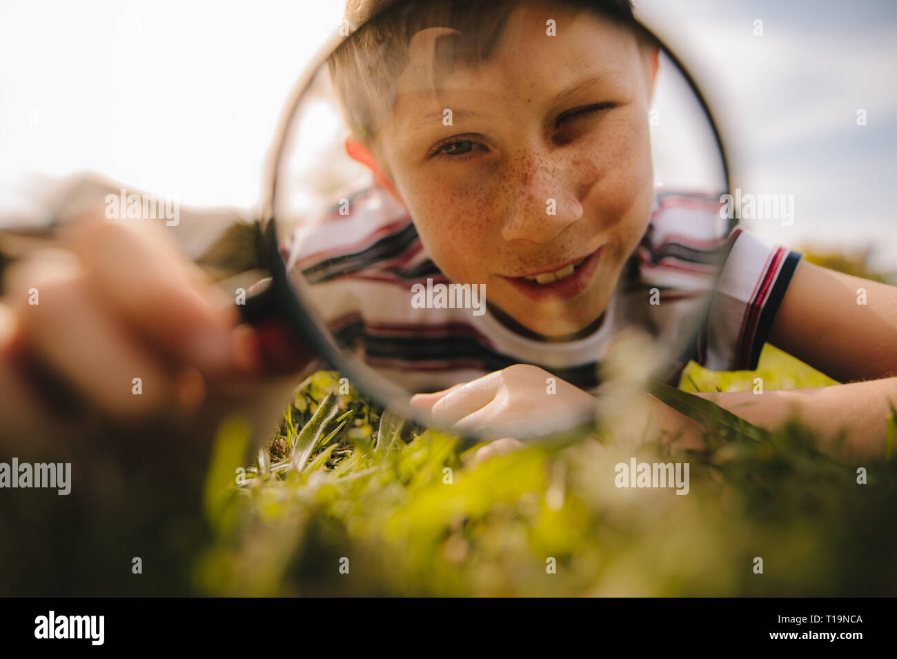 Boy looking through magnifying glass. cute boy exploring with magnifying glass. - Stock Image