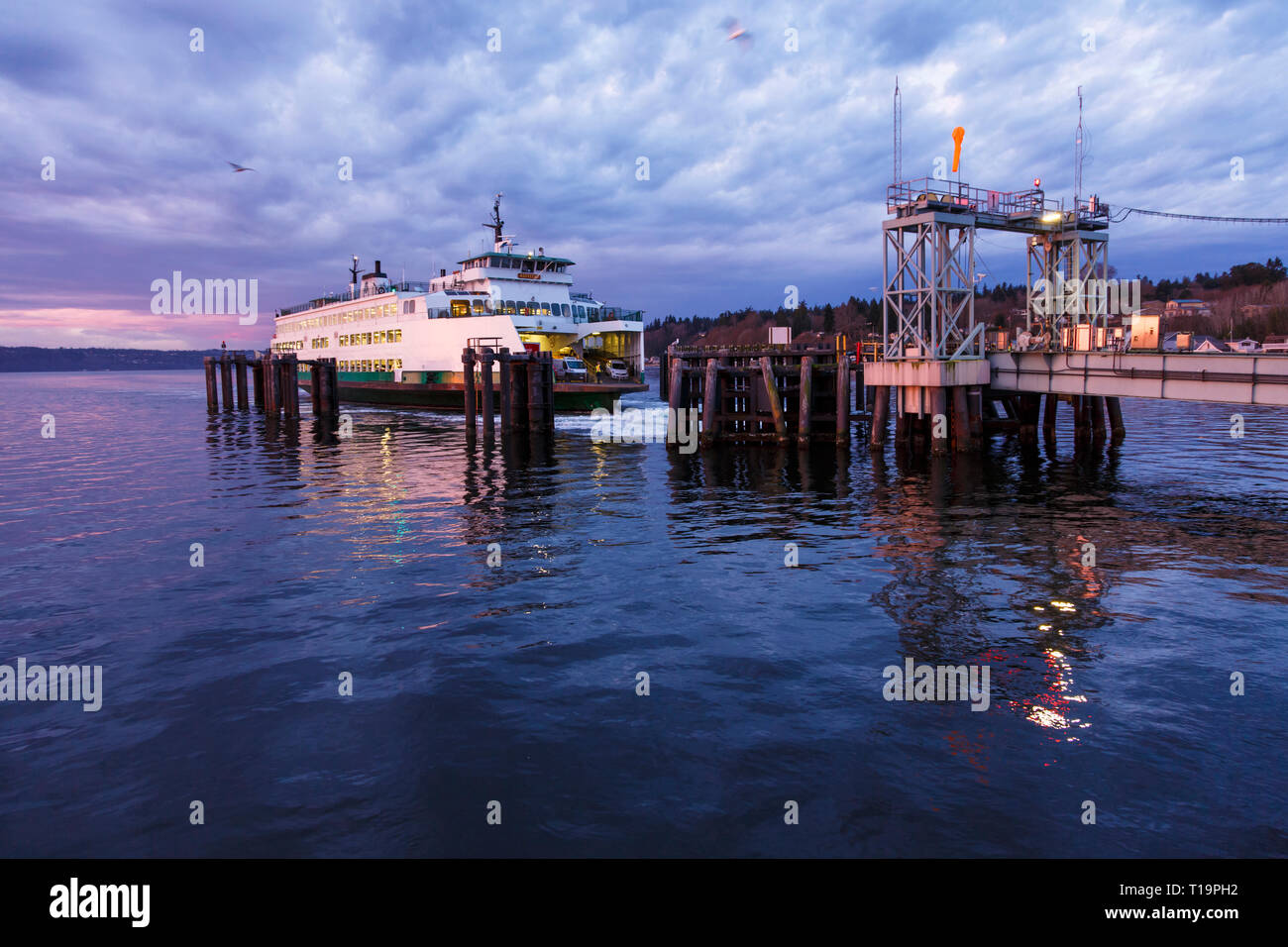 The Washington State ferry Kittitas arriving at the dock in the early morning at sunrise dawn in Clinton, Whidbey Island, WA - Stock Image