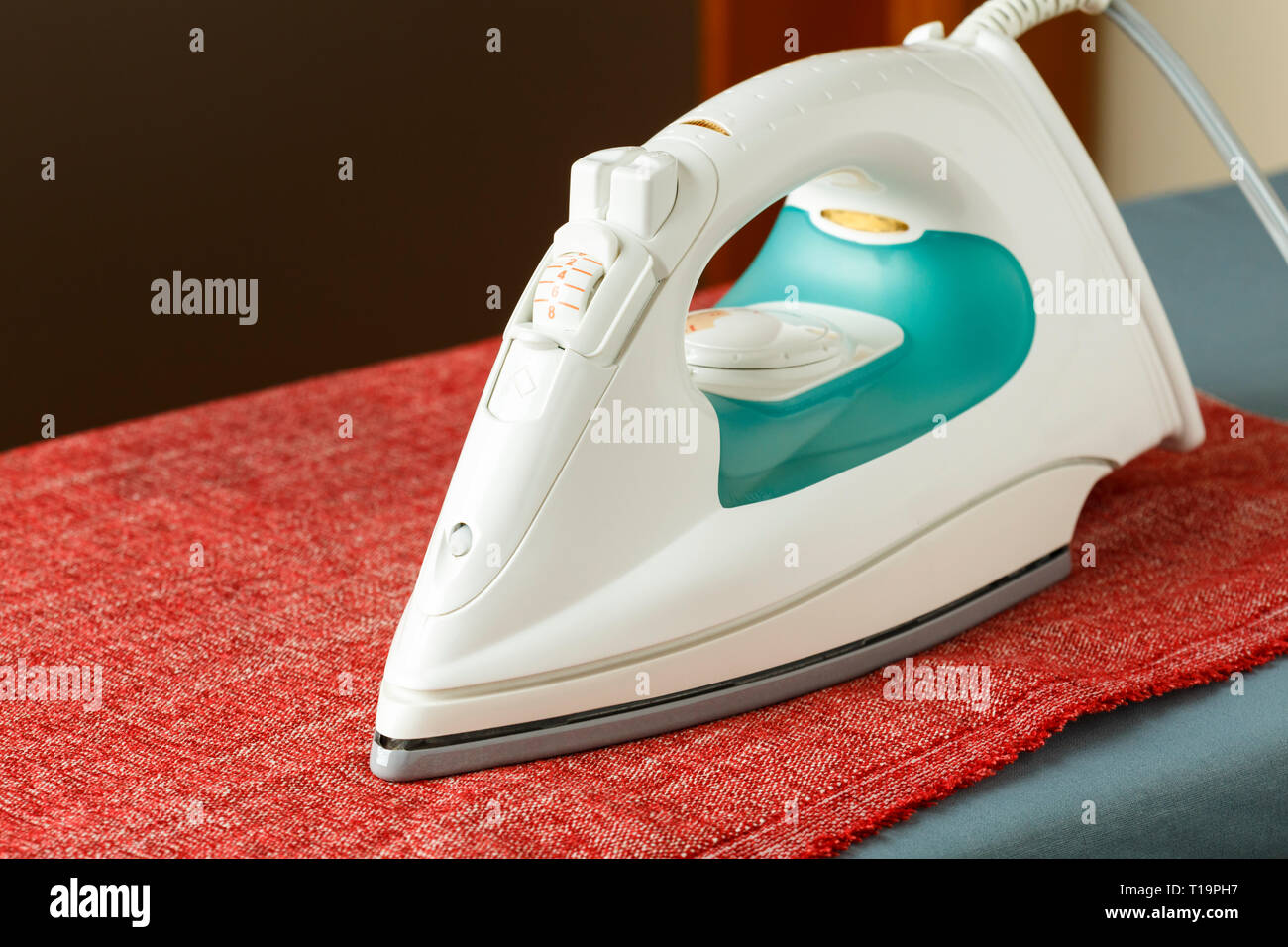 Steam iron resting on cloth fabric on ironing board. Small home electrical appliances housework laundry chores concepts. Ergonomic industrial design. - Stock Image