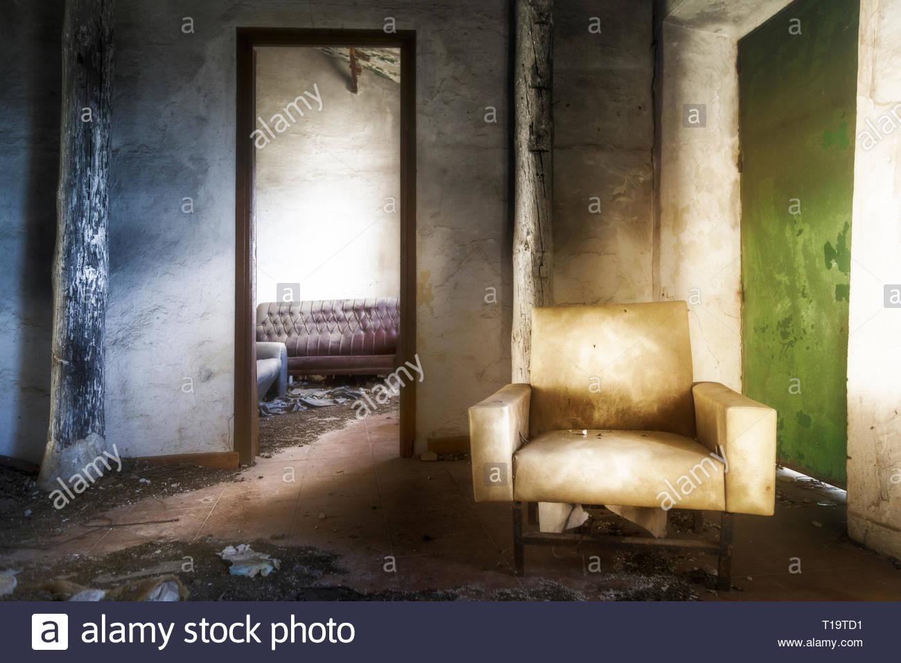 An old armchair in the room of an abandoned country house - Stock Image