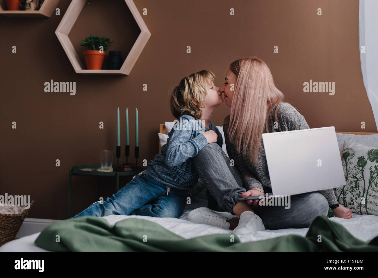 Woman freelancer wiith her son using portable laptop computer at home - Stock Image