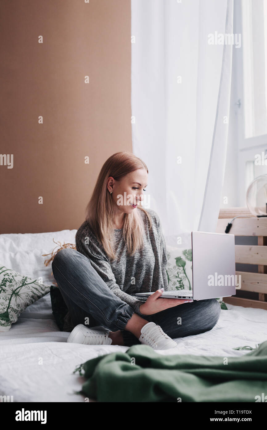 Young woman working on computer in bed. Relaxing at home. - Stock Image