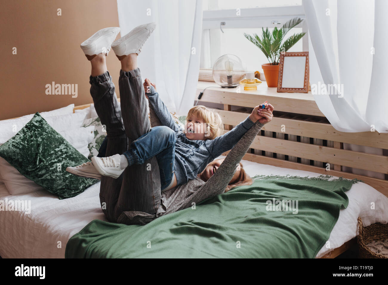 Cheerful little boy having fun with mother on sofa Stock Photo