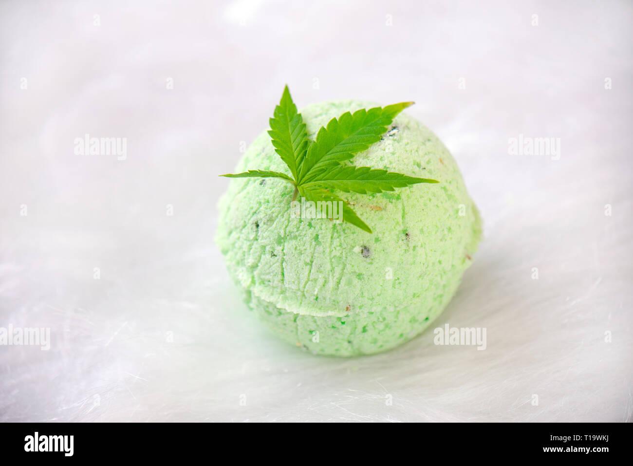 Round green cannabis bath bomb with marijuana leaf isolated on white background - Stock Image