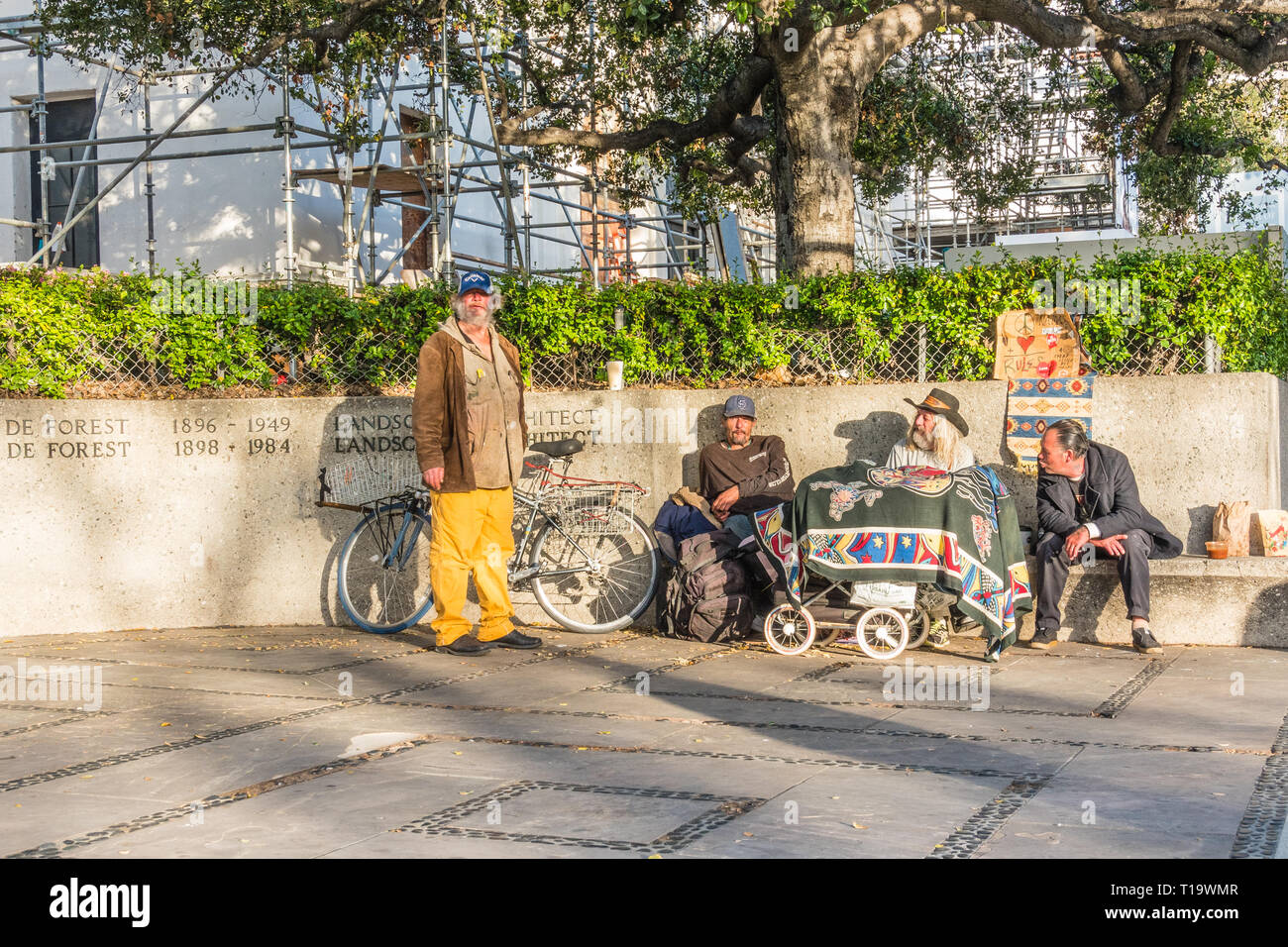Homeless men gathered together on the corner of State Street and Anapamu at sundown. - Stock Image