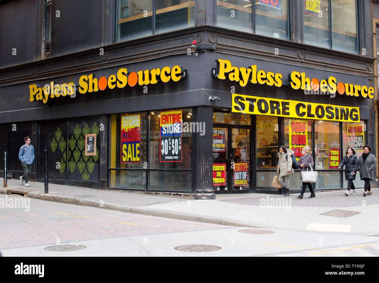 Payless Shoe Source store closing with going out of business signs and motion of people walking by at Downtown Crossing in Boston, Massachusetts USA - Stock Image
