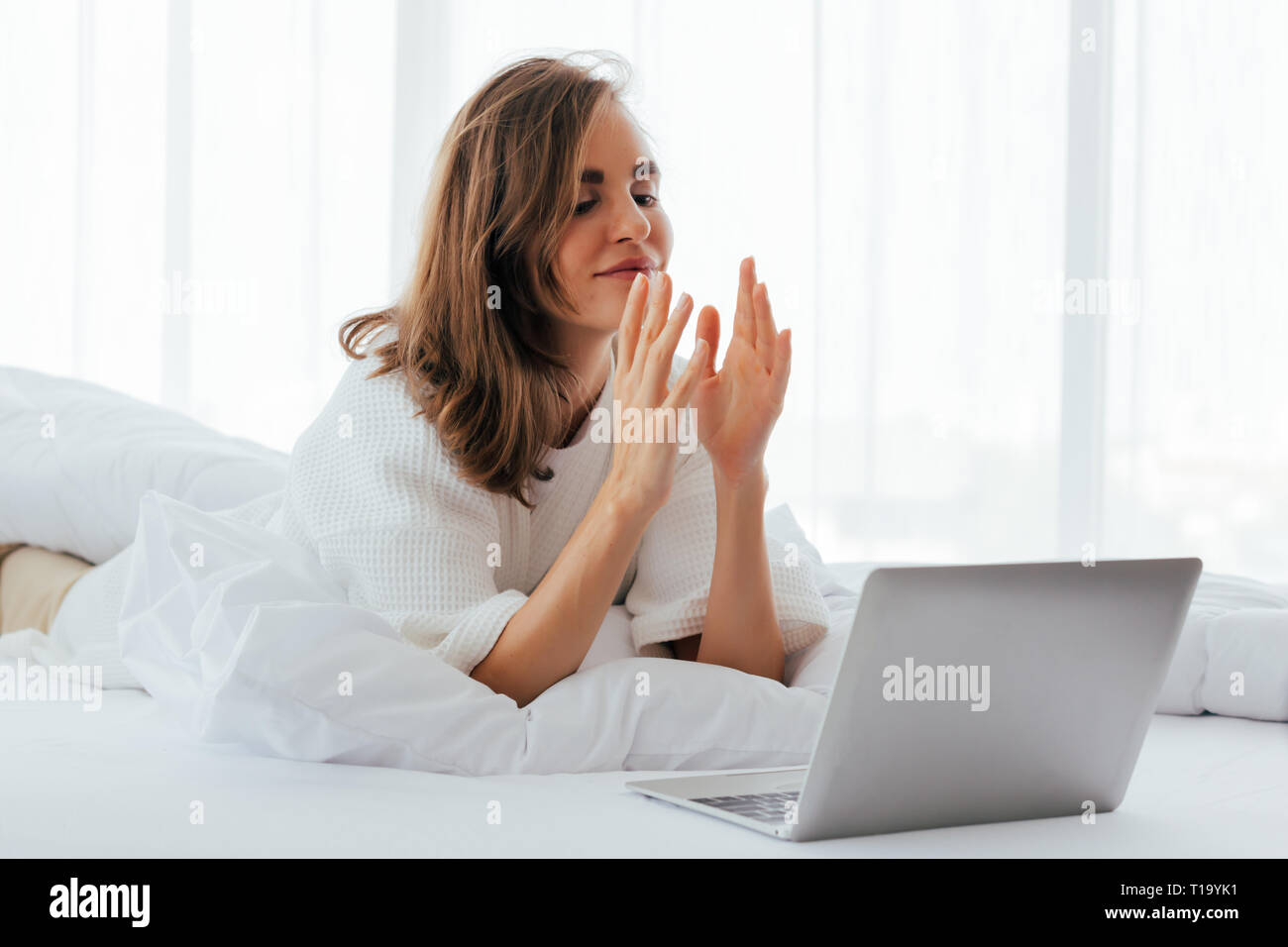 Young woman doing video call on laptop and speaking hand language on bed in light room - Stock Image