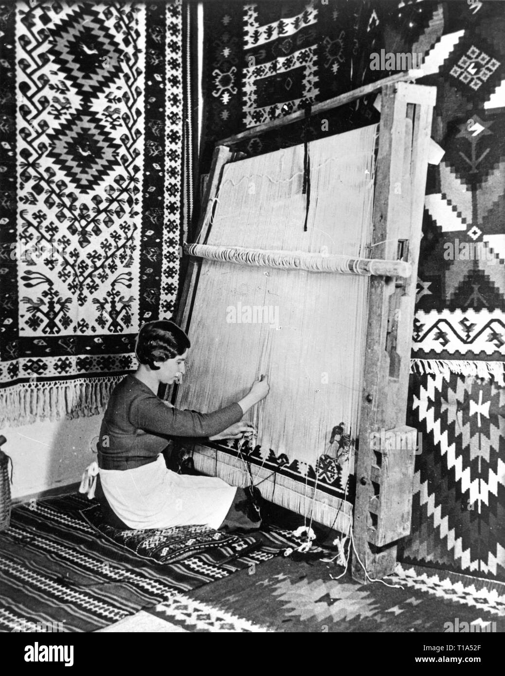 geography / travel historic, Bulgaria, handicraft, a young Bulgarian is weaving of a carpet, circa 1935, Additional-Rights-Clearance-Info-Not-Available - Stock Image