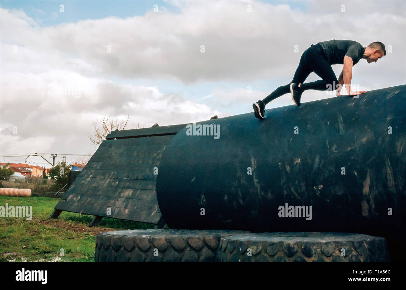 Man in an obstacle course climbing a drum - Stock Image