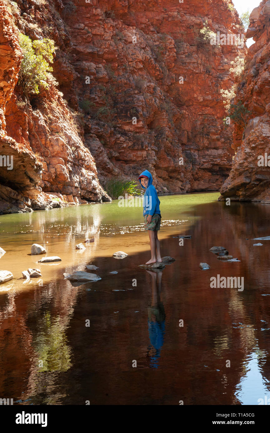 A young boy plays on the stepping stones in the shallows of Simpsons Gap, Northern Territory, Australia - Stock Image