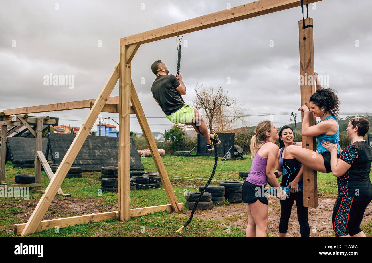 Participants in obstacle course doing pegboard and rope - Stock Image
