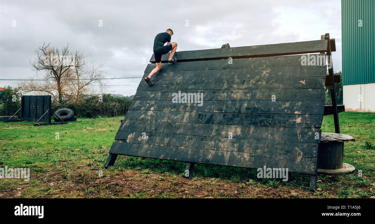 Participant in obstacle course climbing pyramid obstacle - Stock Image