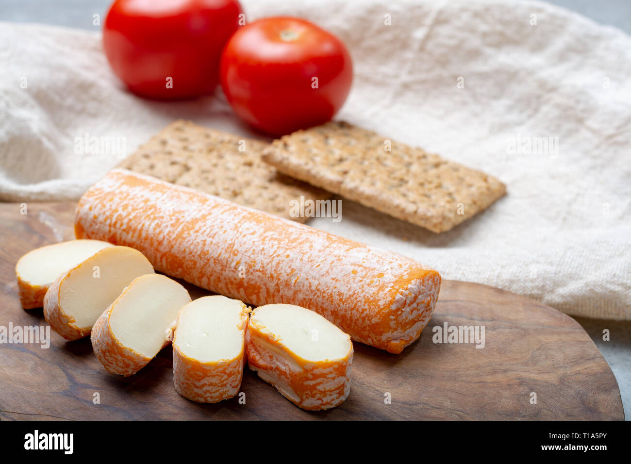 Fagotin cheese with  orange coloured rind made from cow milk in caves of Maredsous abbey, Belgium close up - Stock Image