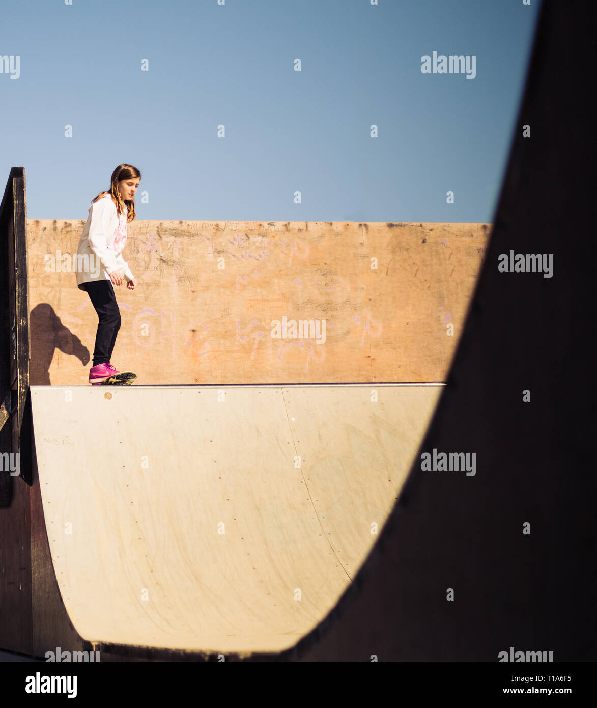 Beautiful teenage girl preparing to jump of the skate ramp on the skate board - Stock Image