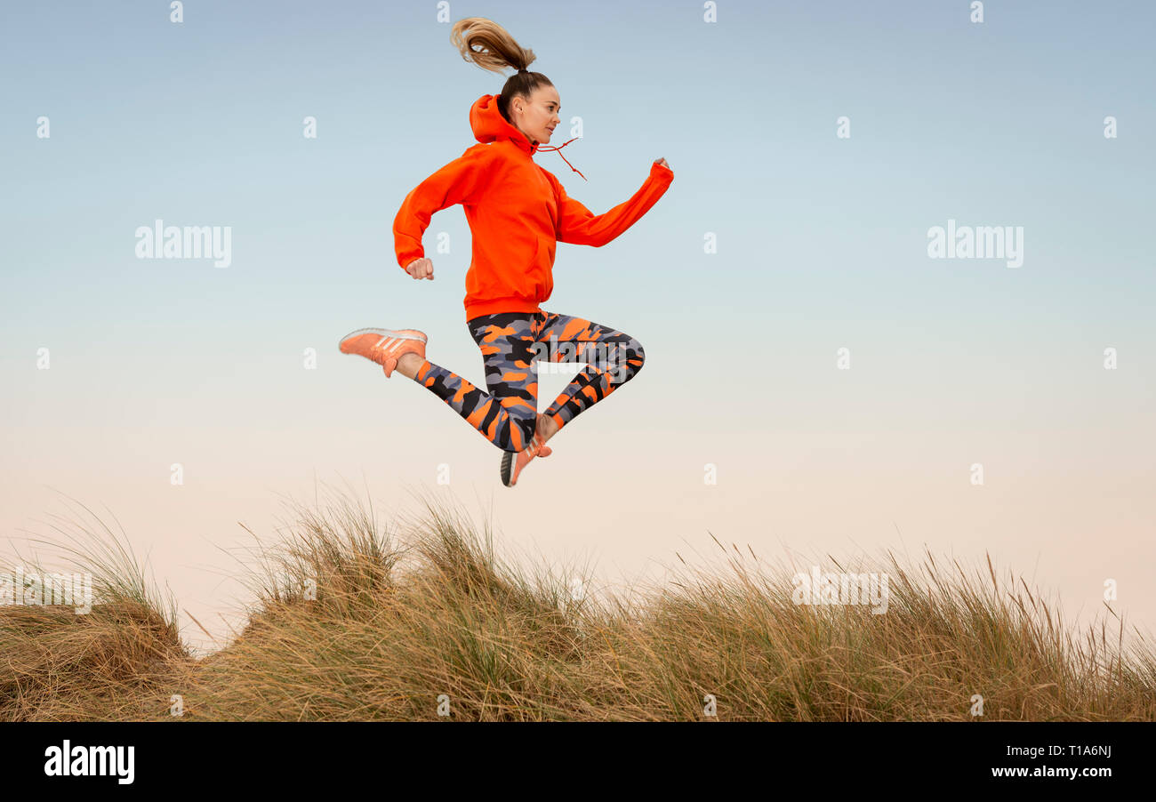 woman running outside, leaping in the air. - Stock Image