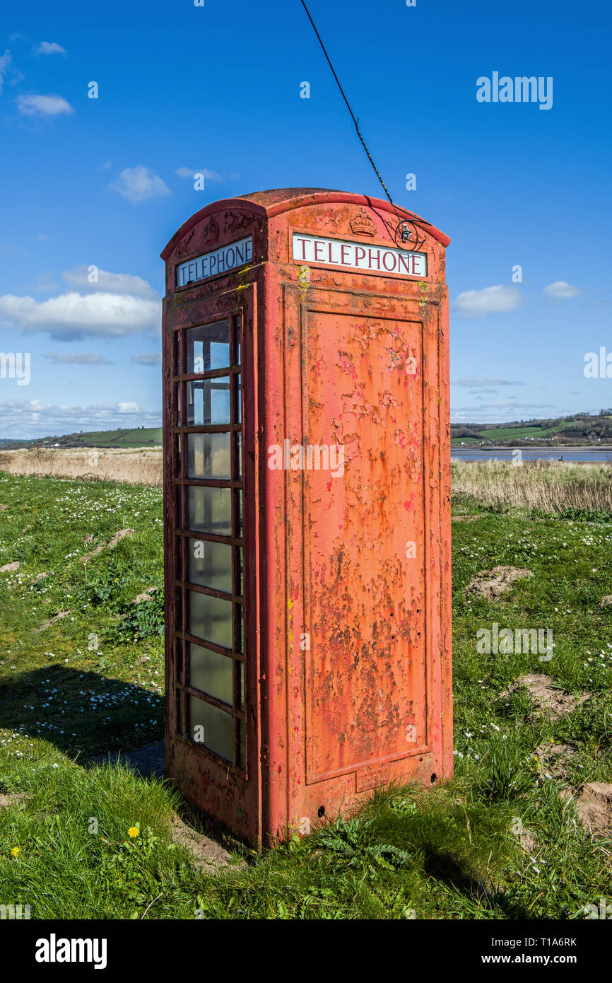 Old red telephone box near the beach at the village of Llansteffan on the Carmarthenshire coast on a bright sunny day. These are slowly becoming rarer - Stock Image