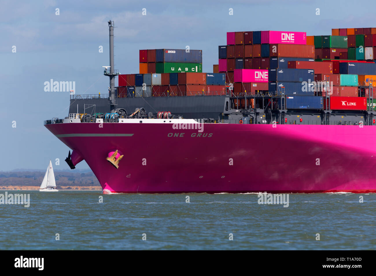 Tug, Phenix,Container,Ship,Grus,ONE,company,entering,Southampton,Water,Terminal,The Solent,off,Cowes,Isle of Wight, England, UK, - Stock Image