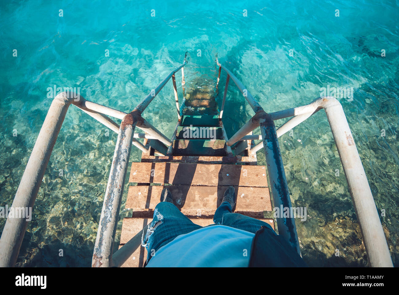 Old vintage metal wooden stairs leading to blue turquoise sea water from beach. Beautiful summer day. Swimming pool with grunge retro stairs on the - Stock Image