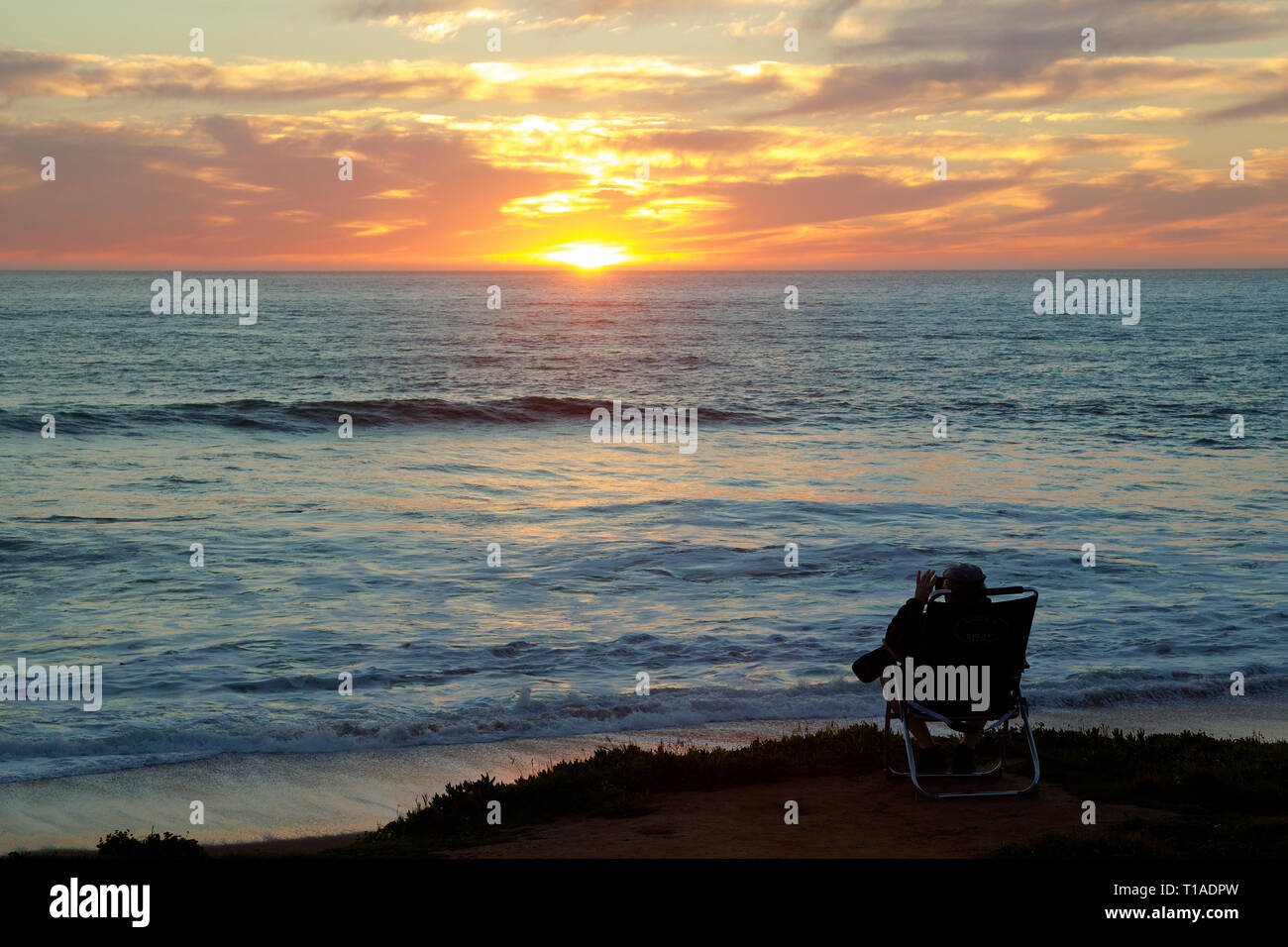 Person sitting in Lawn Chair on Bluff Watching Sunset over the Pacific Ocean - Stock Image