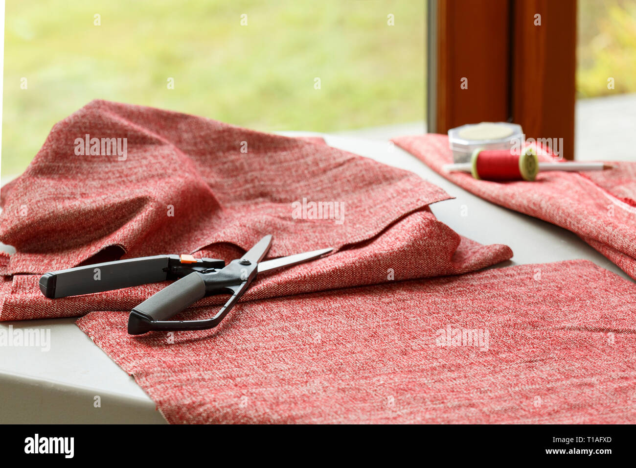 Home sewing crafts projects hobbies. Cloth fabric, scissors, and thread on table. - Stock Image