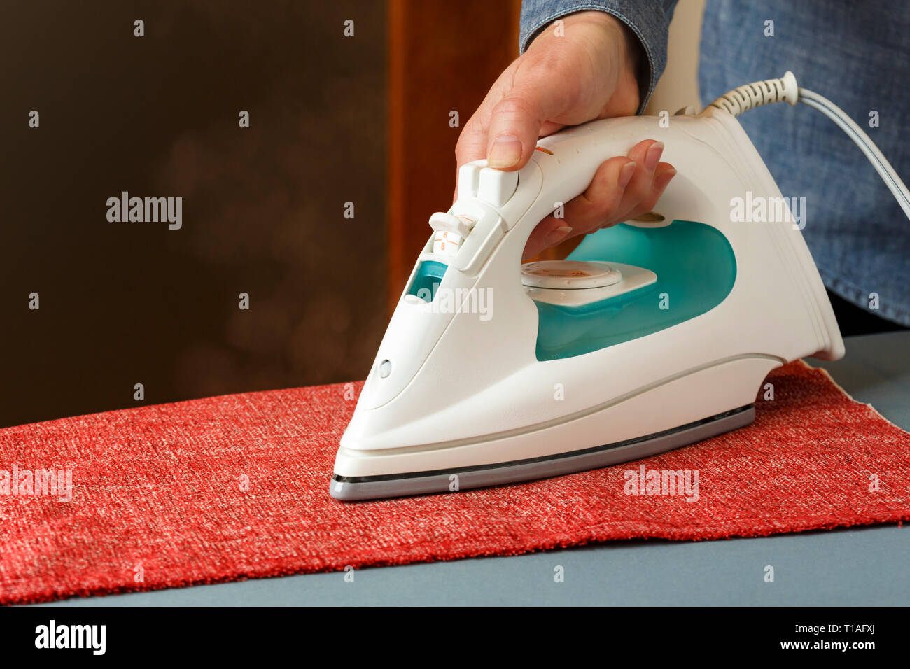 Woman's hand using steam iron ironing cloth fabric on ironing board. Small home electrical appliances people doing housework laundry chores. - Stock Image